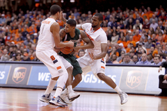 Michael Carter-Williams and James Southerland trap an Eastern Michigan player in Syracuse's victory over the Eagles.